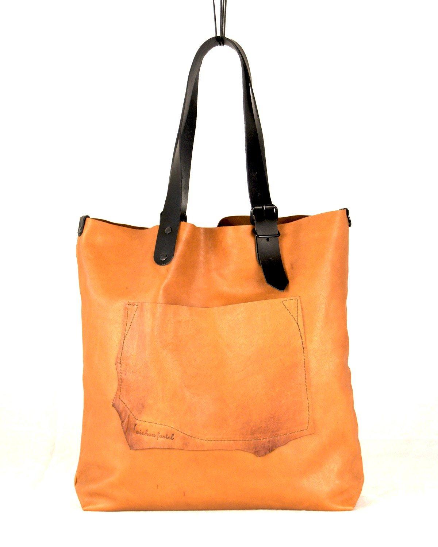 Tote de cuero de color naranja caldera con bolsillo exterior de forma irregular y asas en color arena con hebilla.