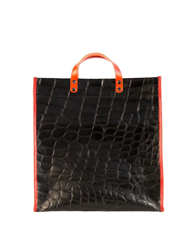 shopping bag de cuero negro con ribetes y asa de mano en rojo.