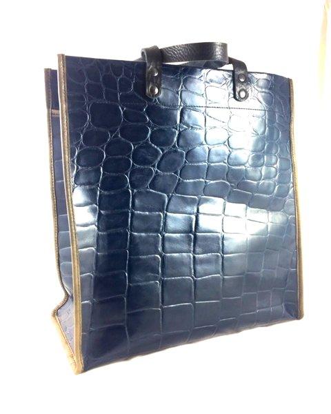 Shopping bag de cuero grabazo reptil color azul marino con asas de mano negras y ribete gris.