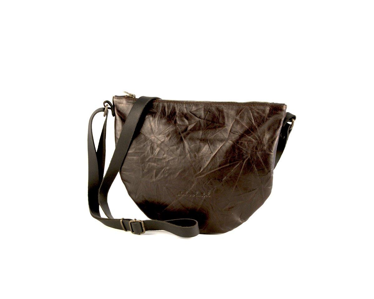 Bandolera de cuero color marrón y textura arrugada, oscurocon forma semicircular.